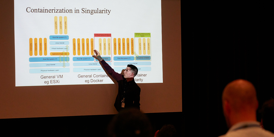 Ian Palmer points to a diagram as his presentation is projected on a big screen