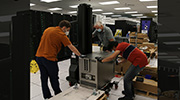 three people install Cerebras components in the HPC machine room