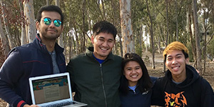 Four UCSD students smile at the camera