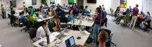 wide shot of hackathon attendees mingling and working on laptops