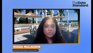 Screen shot of Nisha speaking to the camera with a virtual background behind her