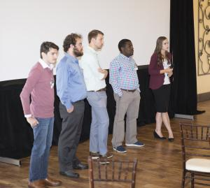 five people stand beneath a big screen taking audience questions