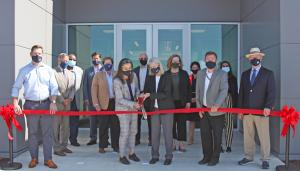 a group of masked people at a ribbon-cutting ceremony outside a building