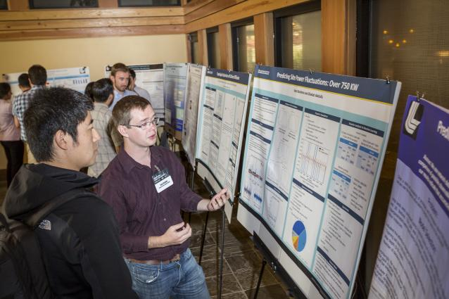 a student discusses his poster with another workshop attendee